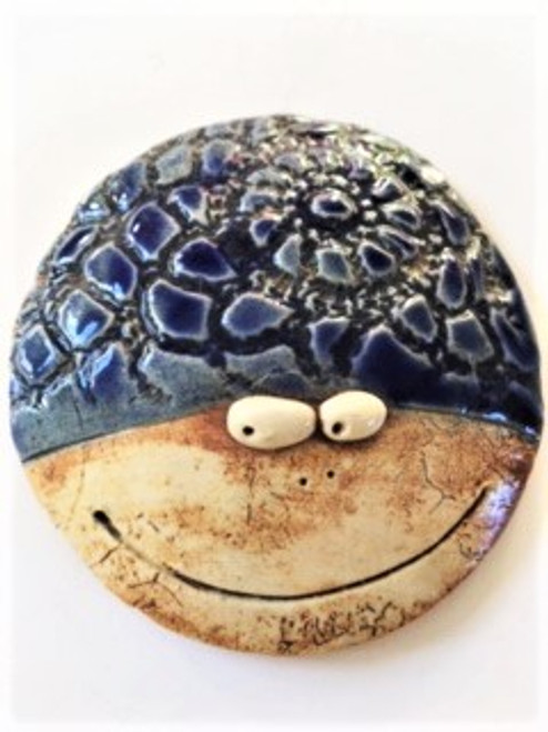This round humbug is hand sculpted (and slightly domed) with high fired clay, stained, glazed and high fired, so they do well indoors or out. The humbug has a blue textured motif on top and whimsical eyes, small nose holes, and a big wide lovely smile .