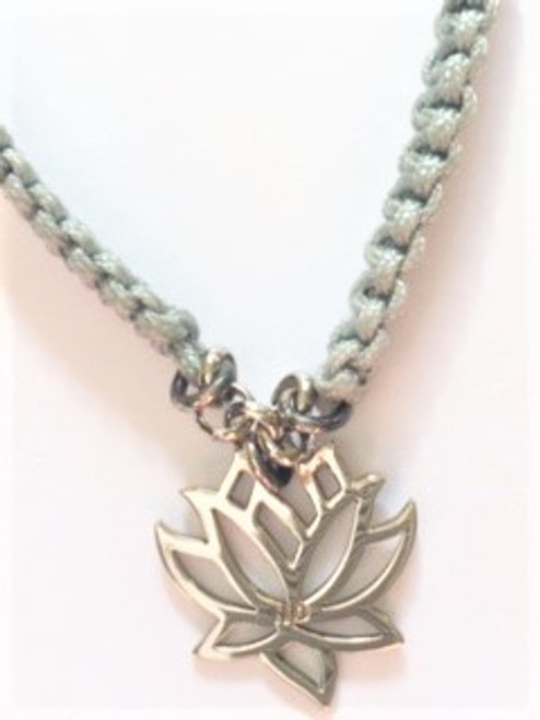 """Macramé light gray cotton cord bracelet with attached sterling silver lotus cutout charm  Macramé width:  .18"""" Lotus charm is .68"""" Bracelet is adjustable using macramé slide Slide ends are finished with coordinating sterling silver bead By Athena Designs"""