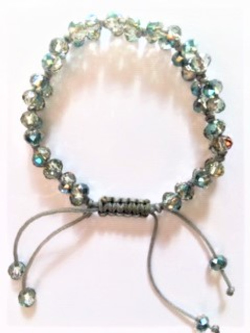 "Macramé with light gray cotton cord and light Montana Blue faceted crystal used with a four bead pattern between macramé knots Bracelet width:  .43"" Bracelet is adjustable using macramé slide Slide ends are finished with coordinating bead By Athena Designs"