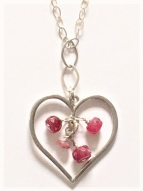 "Sterling silver fine 17"" chain 2"" attached extender with elongated open link end Sterling silver heart cutout (1"" long & 1"" wide) pendant Four rounded, faceted ruby beads dangle inside framed heart cutout  Two elongated open link sterling silver connecters connect pendant to chain Findings in sterling silver By Athena Designs"