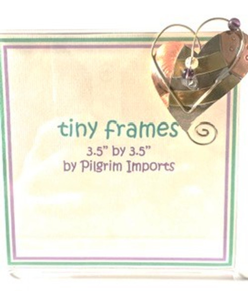 """Clear acrylic picture frame is 3.5"""" x 3.5"""" Metal """"uplift heart"""" design is affixed to top right corner.  Metal is composed of three different metals—nickel, copper, and brass. There is no lead or any other harmful substance in the metals; all metal pieces are designed to be safe as possible, with a minimum of sharp corners and edges. Only lead free solder is used."""