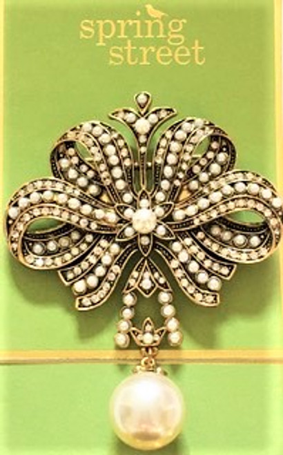 """Stately looking brooch is 2.75"""" wide, 3.5"""" high, & .25"""" deep Cast bronze metal findings Faux cream seed pearls and large round pearl drop at brooch bottom Clear crystals throughout design Lock back safety clasp fastener By Spring Street Design Group"""