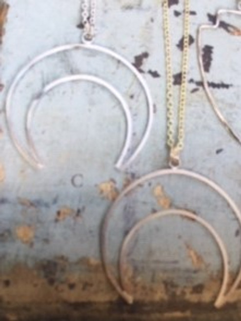 Silver necklace to left.  1.75 inch by 2 inch centerpiece; 30 inch plated sterling silver chain.