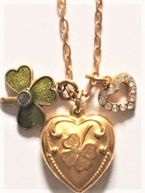 "From the Antiqued Gold Plated Necklace Collection 16"" long chain with 2"" attached extension 14K gold finish over a copper base metal Lobster claw fastener Decorative heart pendant with stamped clover image made with copper base metal findings, green enamel clover with black diamond center crystal, & open heart charm with clear Swarovski crystals  By La Vie Parisienne"