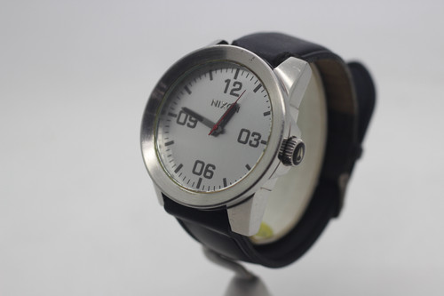 Nixon watch with black leather band.