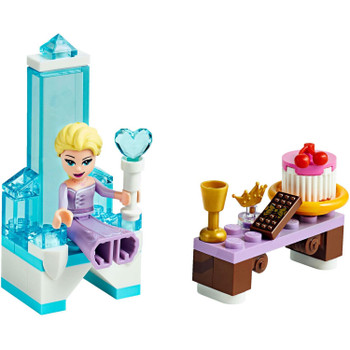 Build a beautiful ice throne and scepter for Elsa and place the crown on her head, then add a table with a buildable cake, chocolate bar and drink for her to enjoy!