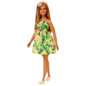 Barbie doll has a curvier body than the original and wears a yellow dress with tropical print, tie and cut-out detail.