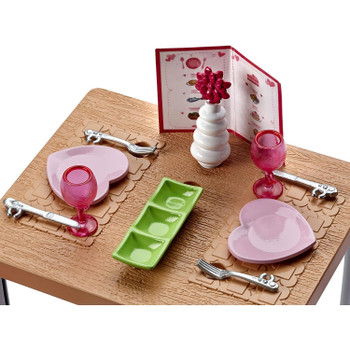 Two heart-shaped plates, two pink glasses, a green serving tray and two utensil sets serve up any meal for two.