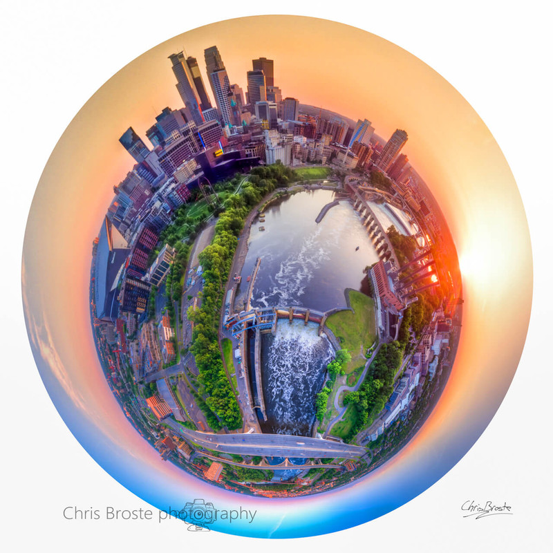 Minneapolis skyline and riverfront from above in a 360 degree planet panorama photograph.
