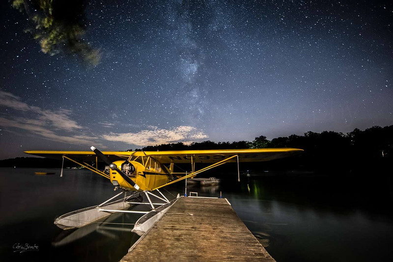 Piper J-3 Cub float plane docked at cabin under milky-way stars.