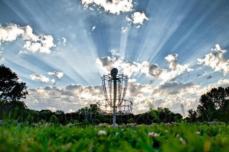 Disc golf chain basket under heavenly sun rays.