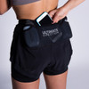 Woman wearing Ultimate Direction Women's Hydro Short, putting phone into center pocket