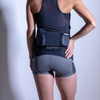 Woman wearing Ultimate Direction Women's Hydro Skin Short, rear view, with hand on hip