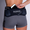Woman wearing Ultimate Direction Women's Hydro Skin Short, putting phone into center pocket