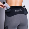 Woman wearing Ultimate Direction Women's Hydro 3/4 Tight, putting water bottle into side pocket