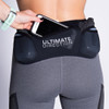 Woman wearing Ultimate Direction Women's Hydro 3/4 Tight, putting phone into center pocket