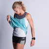 Woman wearing Ultimate Direction Women's Hydro Tank, front view, with tank pulled up to show shorts underneath