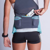 Woman wearing Ultimate Direction Women's Hydro Tank, putting tasty Skratch Labs energy bar into center pocket