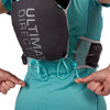 Close up of woman wearing Ultimate Direction Adventure Vesta 5.0, pulling rear adjustment straps