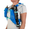 Close up of woman wearing Ultimate Direction Ultra Vesta 5.0, showing trekking poles attached to shoulder strap