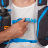 Close up of man wearing Ultimate Direction Adventure Vest 5.0, holding plastic sternum strap buckle