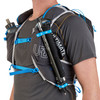 Close up of man wearing Ultimate Direction Adventure Vest 5.0, showing trekking poles attached to shoulder strap