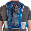 Close up of man wearing Ultimate Direction Mountain Vest 5.0, rear view, with jacket attached to pack with bungee