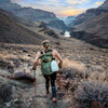 Woman carrying Ultimate Direction Fastpack 40 in the mountains