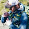 Man placing energy gel in pocket of Ultimate Direction Fastpack 40