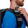 Close up of man placing water bottle in pocket of Ultimate Direction Commuter Briefcase