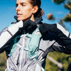 Woman putting water bottle in Ultimate Direction FastpackHer 20, while wearing pack