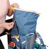 Close up of woman unzipping pocket of Ultimate Direction FastpackHer 30