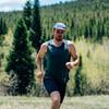 Man running on trail wearing  Ultimate Direction Men's Cumulus Tank