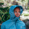 Close up of Ultimate Direction Women's Ultra Jacket, showing woman wearing hood outside