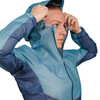 Close up of Ultimate Direction Women's Ultra Jacket, showing woman putting on the hood