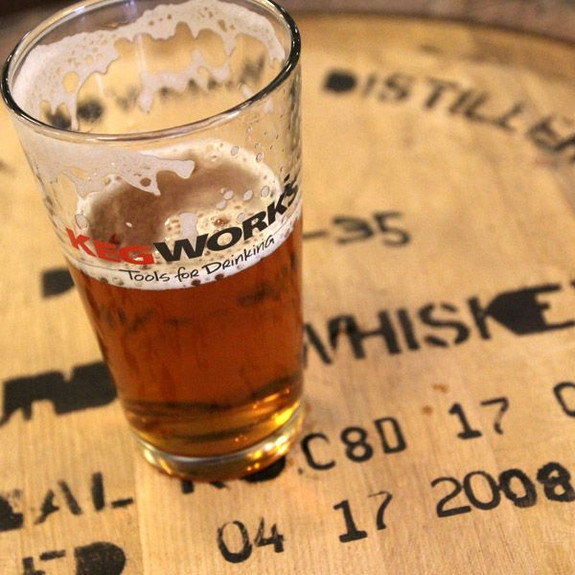KegWorks Tools For Drinking Pint Glass on Whiskey Barrel