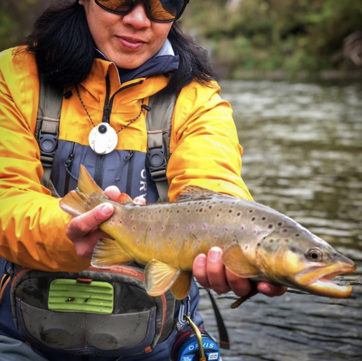 A woman in an orange jacket and waders holding a trout