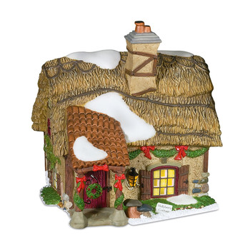 """A thatched roof makes this a special piece. This lighted porcelain residence was designed to accompany Dickens Village by Department 56 and the light thatching allows for a transluscent light to shine through. The piece measures 5.75 x 4.75 x 6"""". It includes a switched cord with bulb."""