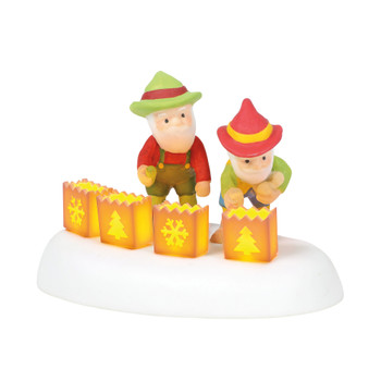 Two of Santa's helpers light the last of the luminaries for the evening. This Village accessory is hand-crafted, hand-painted, porcelain. Battery box included, 2 C batteries required.