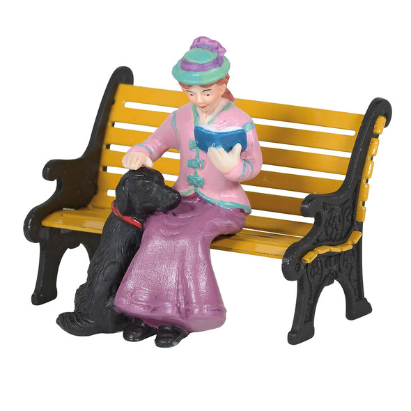 Seated lady pats her black lab dog's head, while reading her book. This general accessory is hand-crafted, hand-painted, porcelain. Bench sold separately.