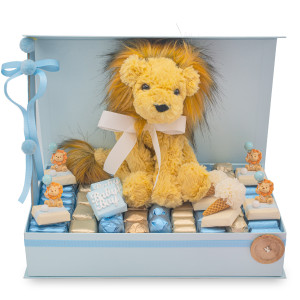 Lion in a blue box on a bed of individually wrapped chocolates in blue and ivory with decorated chocolates throughout