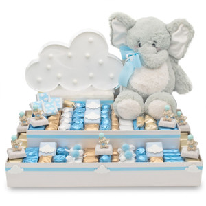 Ivory tray with cloud light and large elephant plush on a bed of blue white and ivory individually wrapped chocolates
