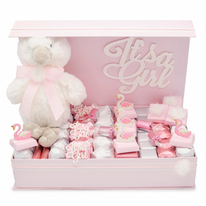 Pink magnet box open with large white acrylic Its a girl sign behind a small white swan plush on a bed of chocolate with alternating foil wrapping of pink and white and 11 decorated chocolate favors