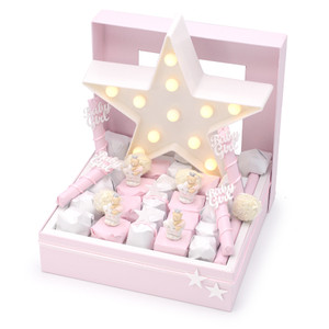 IVORY WINDOW BOX WITH ALTERNATING ROWS OF Pink AND WHITE INDIVIDUALLY WRAPPED CHOCOLATES WITH A LARGE STAR LIGHT