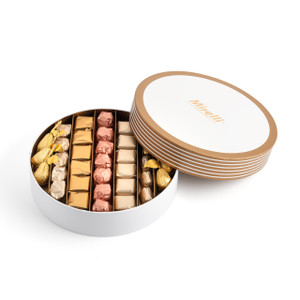 Open white box with alternating gold and white bands on the lid resting on top displaying rows of gold, ivory, and rose gold chocolates