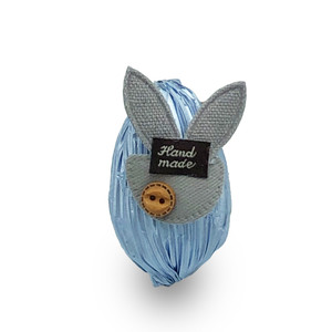 blue egg wrapped with blue crinkle paper adorn with grey cloth rabbit head and small wooden button