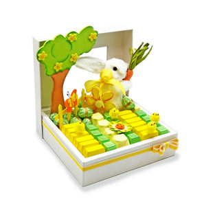 Ivory Mirelli Window Box decorated with green, yellow wrapped chocolates with a straw bunny