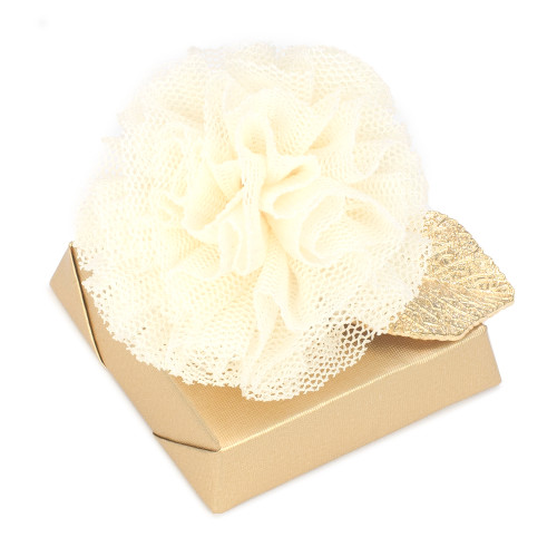square chocolate with gold leaf under white tuul pom pom