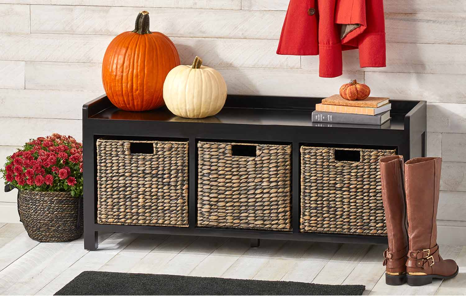 black bench with woven baskets and pumpkins mums for entryway