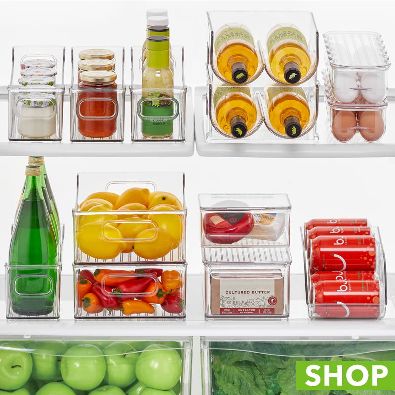 Open refrigerator shelves with clear storage bins for fruits and veggies
